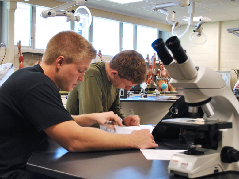 students working in a biology lab near a microscope